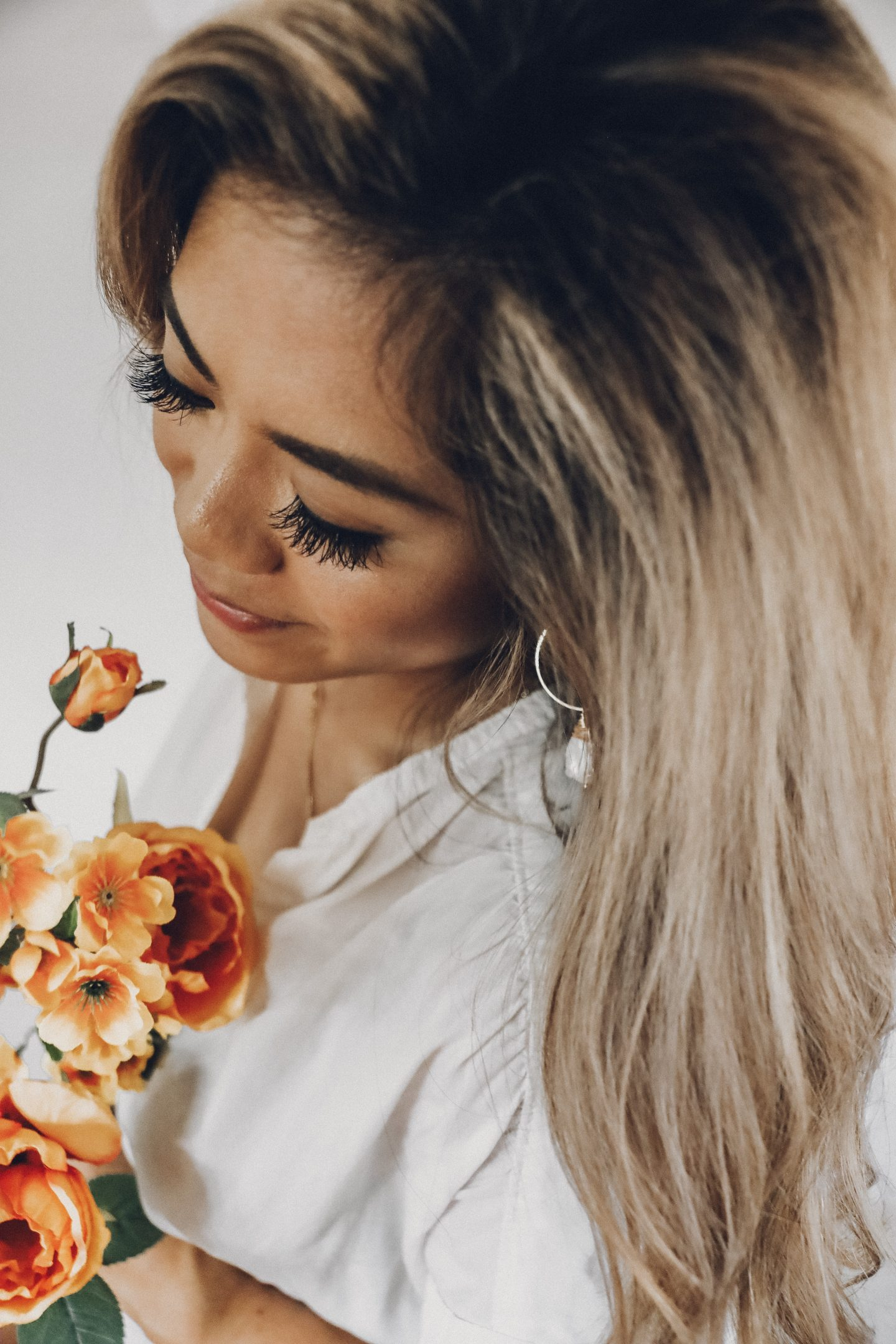 Girl with long hair angled at the camera, holding and looking down at orange flowers